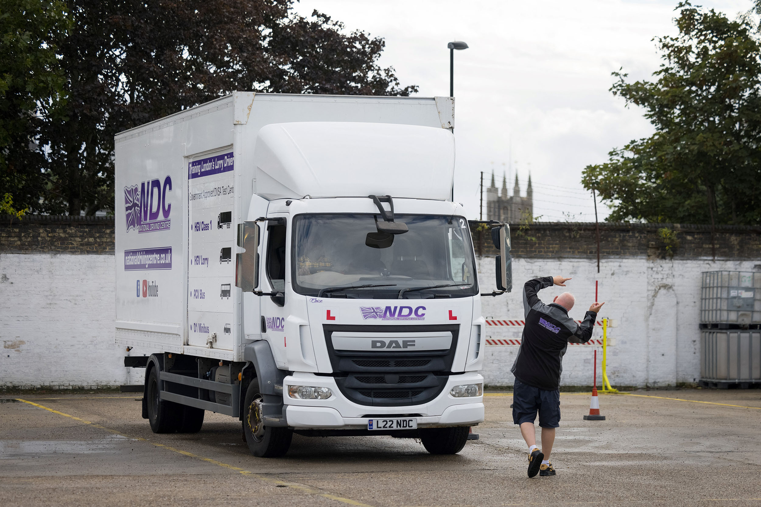 A HGV (Heavy Goods Vehicle) driving instructor (L) gives instructions to a learner lorry driver as he prepares to reverse a lorry at National Driving Centre in Croydon, south London on October 1, 2021. – The British government said last month it will simplify the procedure to qualify as a lorry driver to tackle widespread delivery problems hitting retail businesses. Hauliers and business associations have blamed empty shelves in shops on an exodus of EU national drivers due to Brexit as well as virus-related restrictions.